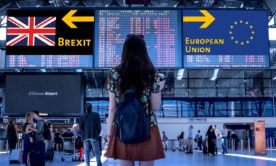 A young woman stands in an airport looking at signs