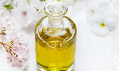 A glass bottle with CBD oil in it. there are white flowers in the top left corner