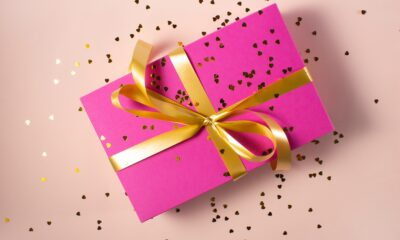 A present wrapped in pink paper with a gold ribbon and bow. There is glitter sprinkled across the top