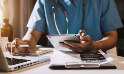 Doctor working with mobile phone and stethoscope in modern office