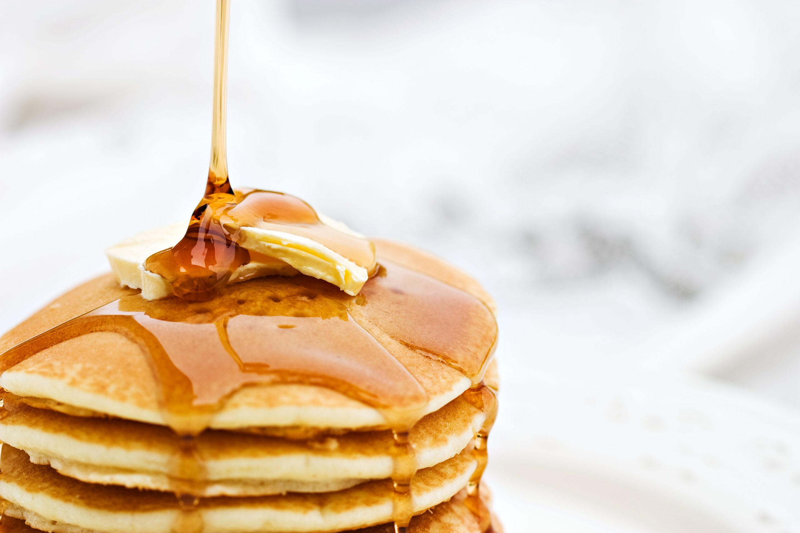 A stack of panckaes with butter and syrup.