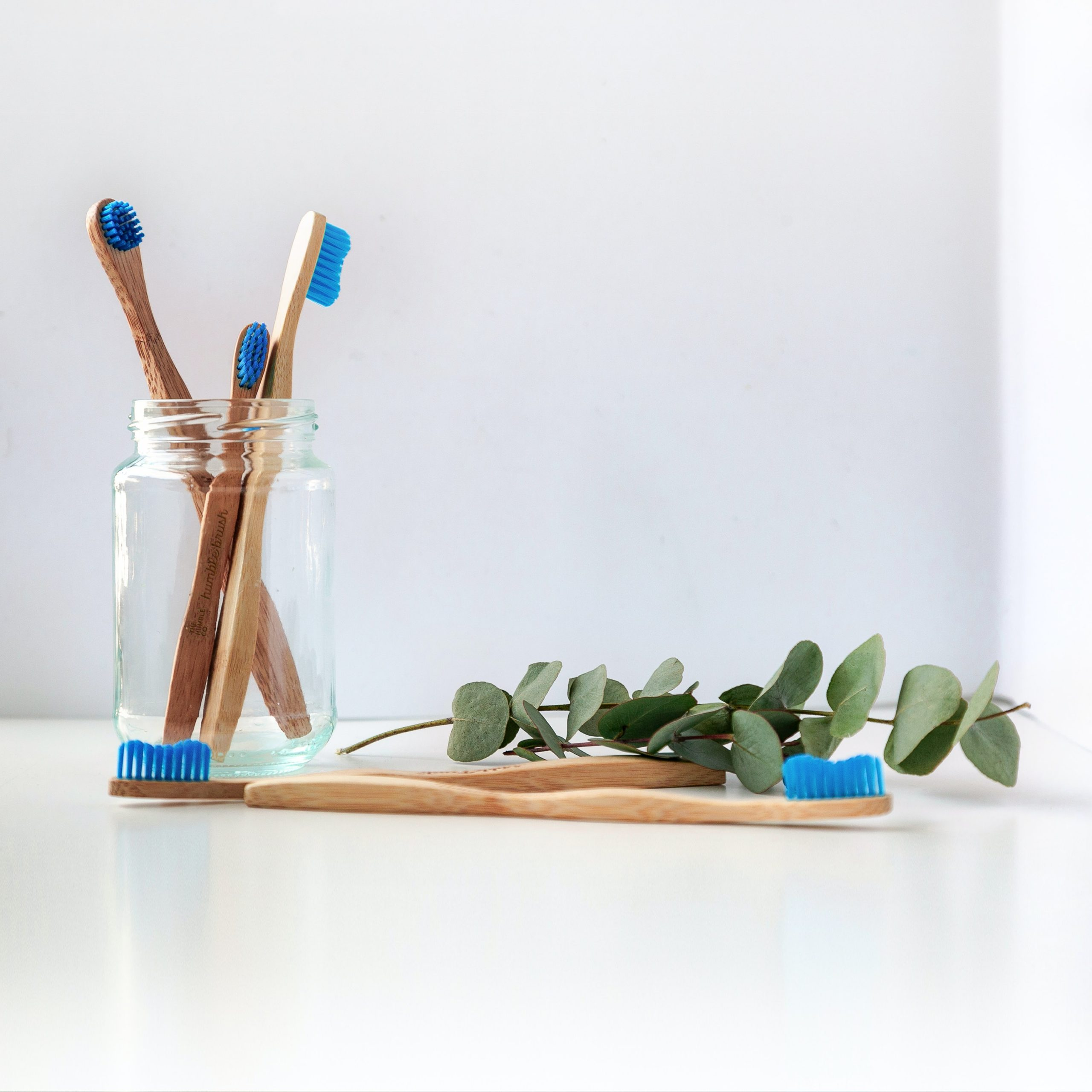 Four wooden toothbrushes in a glass jar with a sprig of ivy near them