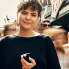 A woman holding a black vape device on a busy street