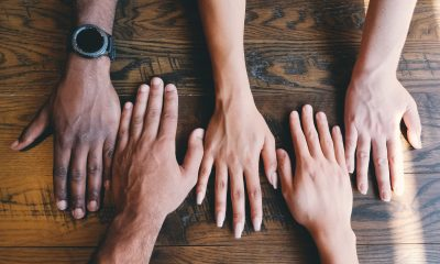 Two rows of hands on a wooden table in lines