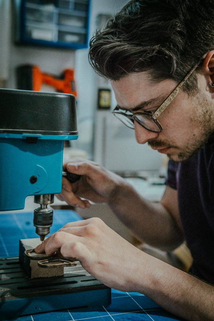 A man with dark hair and glasses is using blue machinery
