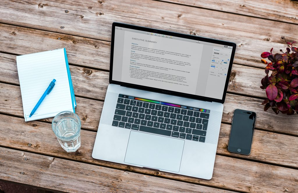 A notepad next to a laptop computer focused on funding. There is a glass of water and phone beside the laptop and purple flowers to the right.