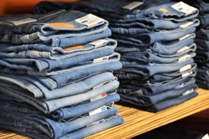 Two piles of blue denim jeans on a wooden shelf lined up to be sold.