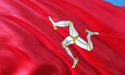 A red Isle of Man flag with three white legs against a blue sky