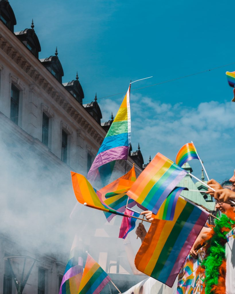 A building against a blue sky. There is a row of brightly coloured gay pride flags and smoke.