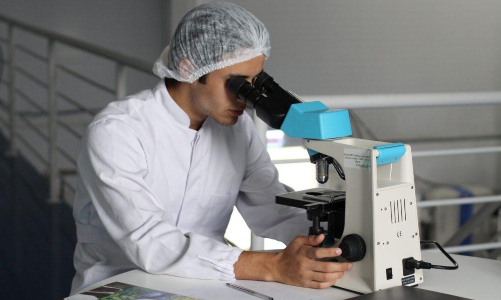 White man using microscope