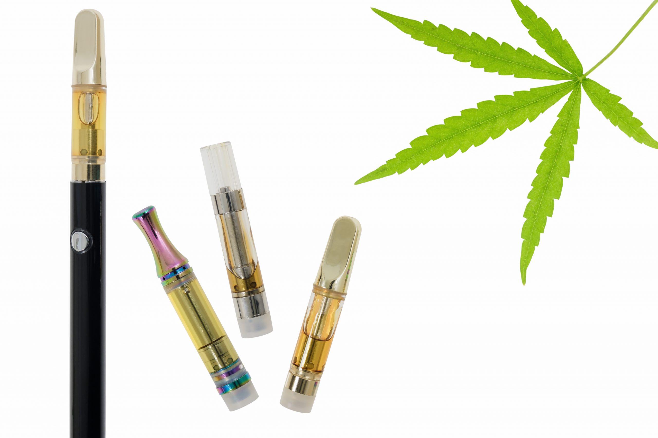 Four cannabis vape carts and a leaf