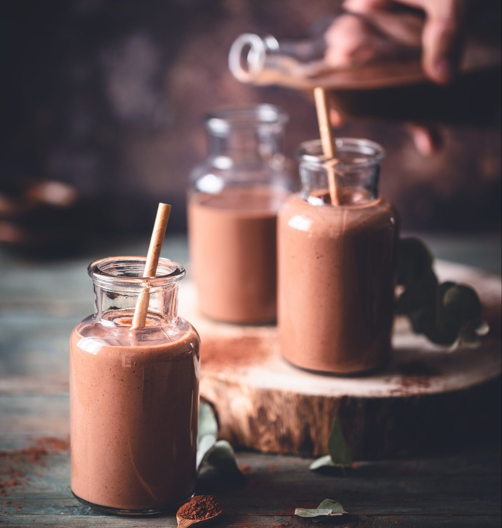Chocolate milkshake presented in a milk bottle with a straw.